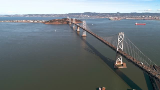 the aerial view of the treasure island over the oakland bay bridge. san francisco, california - baia di san francisco video stock e b–roll
