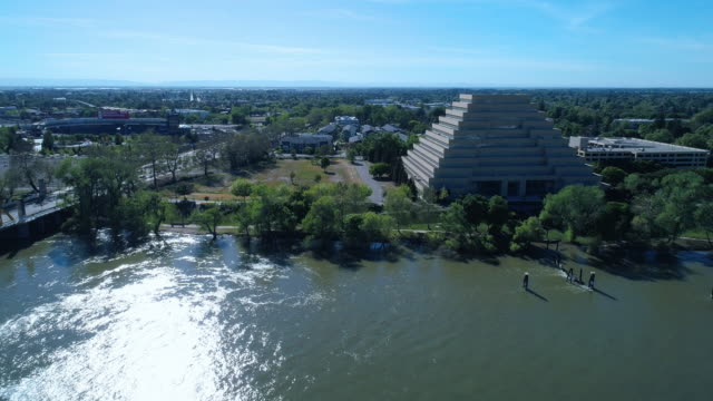 the aerial view of the ziggurat building in sacramento, california. drone video with the wide-orbit, backward and tilting-down complex cinematic camera motion. - ziggurat stock videos and b-roll footage