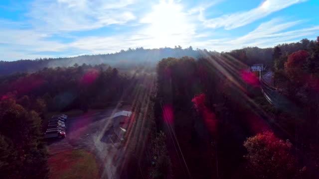 satellitvyn på dimman över bergets skog i appalacherna, poconos, pennsylvania, vid tidig morgon under säsongen hösten bladverk. fotograferar mot solen, med linsen flare och sunbeamsaerial drone video. - poconobergen bildbanksvideor och videomaterial från bakom kulisserna