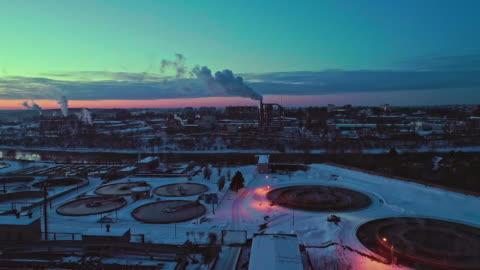 vídeos y material grabado en eventos de stock de la vista aérea de las instalaciones de tratamiento de aguas residuales y planta de energía en la zona industrial al atardecer en invierno. - bielorrusia