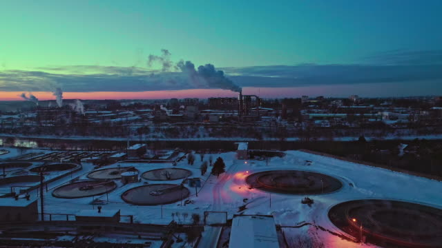 The aerial view on the waste wastewater treatment facilities and power plant in the industrial zone at sunset in winter.