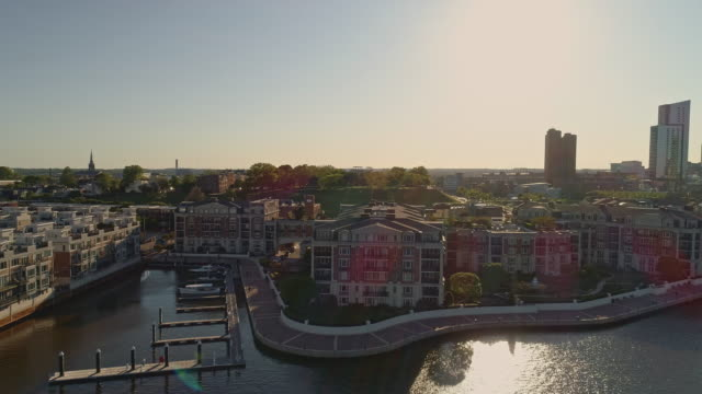 the aerial view on waterfront of harbor view residential district and marina at patapsco river in baltimore, maryland, usa, at sunset. drone video with the forward camera motion. - baltimore maryland stock videos & royalty-free footage