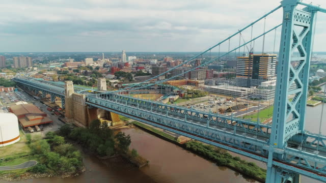the aerial view over the benjamin franklin bridge across the delaware river to the waterfront and industrial zones in camden, new jersey. drone video with the ascending camera motion. - new jersey stock videos & royalty-free footage