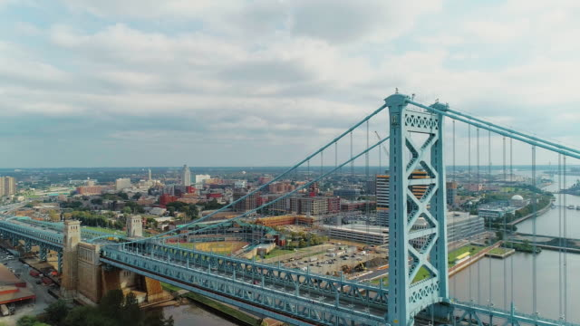vídeos de stock e filmes b-roll de the aerial view over the benjamin franklin bridge across the delaware river to the waterfront and industrial zones in camden, new jersey. drone video with the descending camera motion. - ponte ben franklin