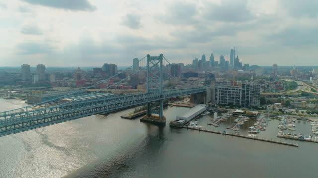 デラウェア川に架かるベンジャミン・フランクリン橋を渡る空中写真で、ニュージャージー州カムデンのウォーターフロントと工業地帯へ。後方カメラの動きを持つドローンビデオ。 - ベンフランクリン橋点の映像素材/bロール