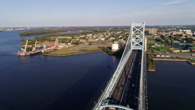 the aerial view over the benjamin franklin bridge across the delaware river from philadelphia, pa to cadmen, nj - north stock videos and b-roll footage