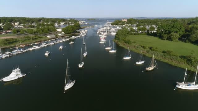 vídeos de stock, filmes e b-roll de a vista aérea com o iate na marina em mamaroneck, westchester, nova york, eua. - lago reflection