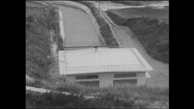the aichi canal winds through a rural area in japan. - wasserpumpanlage stock-videos und b-roll-filmmaterial