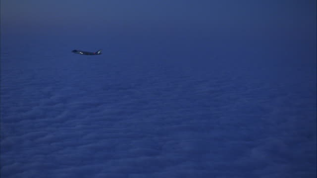 The Air Force One jet flies above a thick cloud cover.
