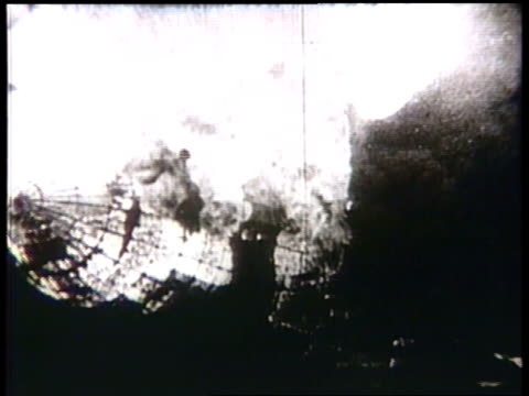 the airship hindenburg ignites into  towering flames and crumples to the ground. - ヒンデンブルク号点の映像素材/bロール