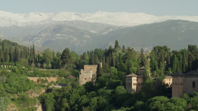 vídeos de stock e filmes b-roll de ls pan the alhambra of granada with the sierra nevada mountain range in background; pan starts  at the generalife and covers the entire complex, ending at the alcazaba - frio