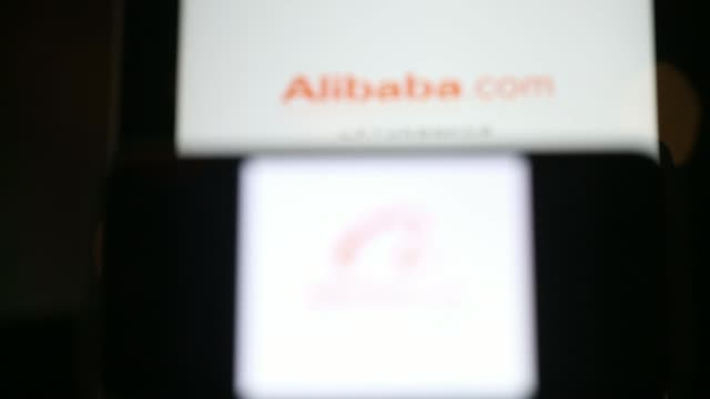 stockvideo's en b-roll-footage met the alibaba group holding ltd application loading page is displayed on an apple inc ipad rear and iphone 5s in an arranged photograph in hong kong... - goede staat