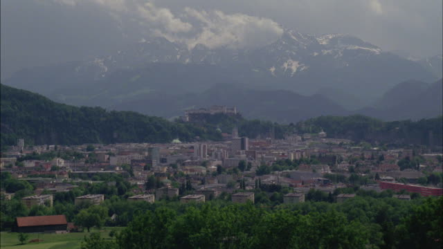 the alps mountains rise above the city of vienna. - ウィーン点の映像素材/bロール