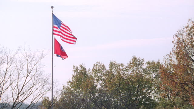 vídeos de stock e filmes b-roll de the american and tennessee state flags wave from a flagpole. - tennessee