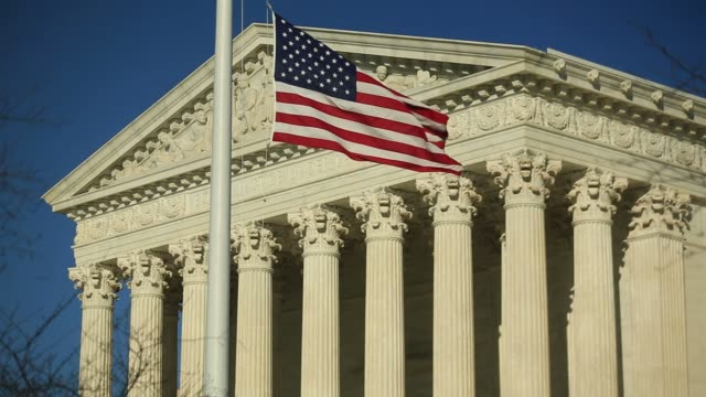 the american flag flies at half-staff in front of the u.s. supreme court building in washington, d.c., u.s., on tuesday, feb. 16, 2016 justice... - u.s. supreme court stock videos & royalty-free footage