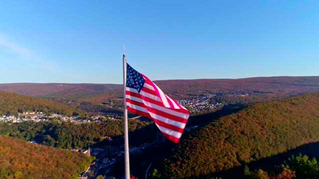 the american flag flying on the high flagpole over the appalachian mountains, poconos, pennsylvania, near by jim thorpe - pennsylvania stock videos & royalty-free footage