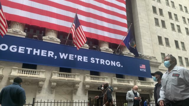the american flag is hung from the new york stock exchange in lower manhattan on the first day that traders are allowed back onto the historic floor... - market stock videos & royalty-free footage