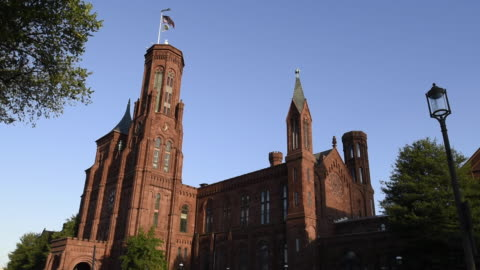 the american flag waves atop a smithsonian castle turret. - smithsonian institution stock videos & royalty-free footage