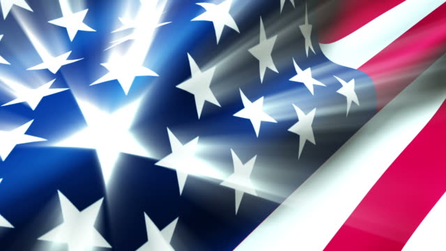 stockvideo's en b-roll-footage met the american flag waves in the breeze as light rays shoot from the stars. - nationale vlag