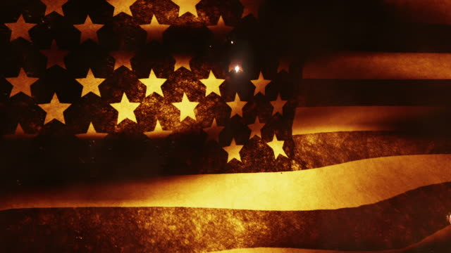 The American flag waves in the breeze as rockets and fireworks burst.