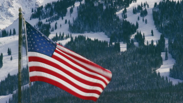 the american flag waves majestically on a sunny afternoon with a colorado mountain ski resort in winter in the background - colorado stock videos & royalty-free footage
