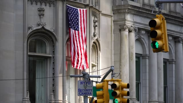 the american national flag is hoisted at ukrainian institute building wall at fifth avenue uptown manhattan in new york city. - hoisting stock videos & royalty-free footage