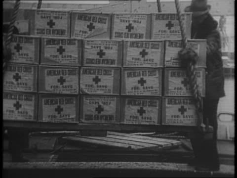 the american ship ss cold harbor in baltimore port / man painting the red cross on the side of the ship / montage of red cross nurses packing... - port of baltimore stock videos & royalty-free footage