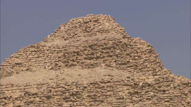 the ancient saqqara pyramid contrasts against a blue sky. - saqqara stock videos and b-roll footage