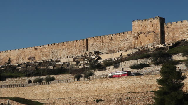The ancient walls surrounding the Old City of Jerusalem loom over houses and traffic.