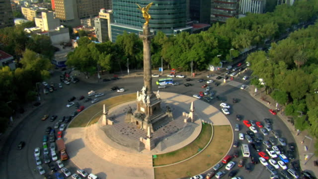 the angel of independence victory column w/ traffic moving around roundabout skyscrapers buildings bg - angel点の映像素材/bロール
