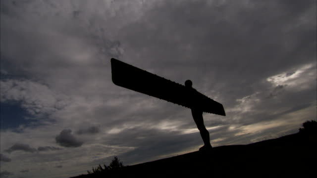 the angel of the north statue stands in stark silhouette against a stormy sky. available in hd. - angel of the north stock videos and b-roll footage