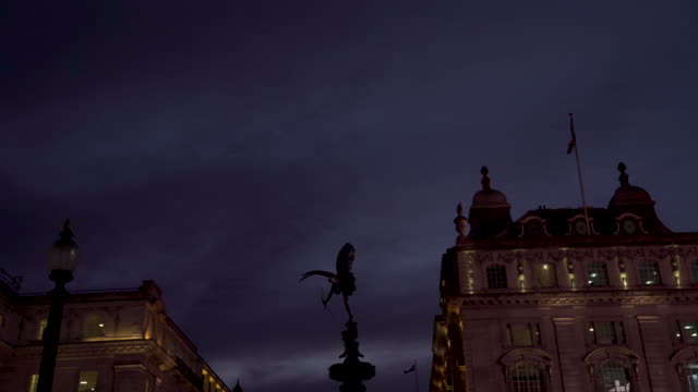 vídeos de stock, filmes e b-roll de the anteros sculpture atop the shaftesbury memorial, piccadilly circus, against a cloudy night sky - cupido