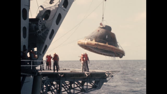 vídeos de stock e filmes b-roll de the apollo 11 space capsule is being lifted from the ocean floor onto the uss hornet. the apollo 11 was the first manned space craft due to land and... - prt