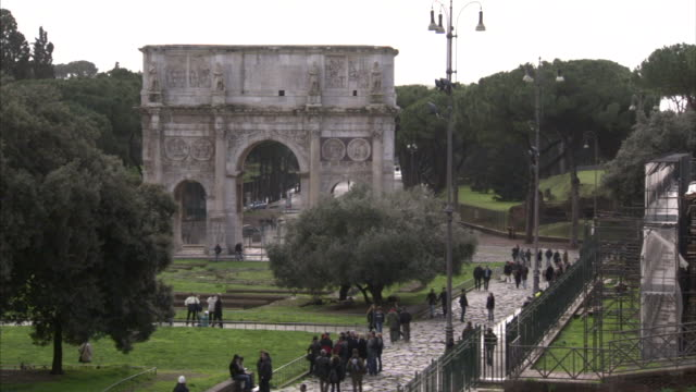 the arch of constantine triumphal arch in rome off center unidentifiable people tourists walking on streets lower frame - arch of constantine stock videos and b-roll footage