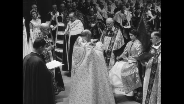 the archbishop of canterbury assisted by the dean of westminster places the armills on queen elizabeth ii as she sits upon king edward's chair at her... - coronation stock videos and b-roll footage
