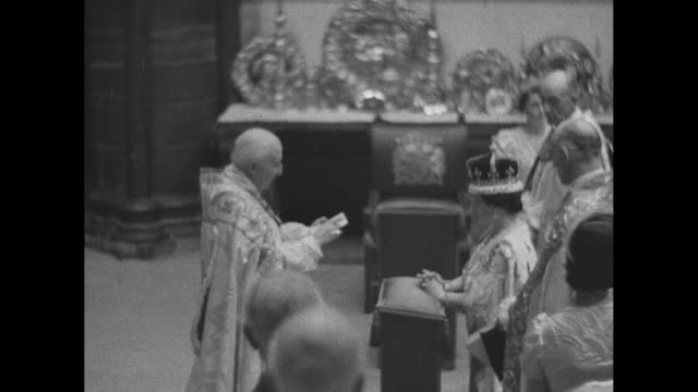 the archbishop of canterbury places the crown on elizabeth's head / queen mary talks to princess elizabeth princess margaret stands next to princess... - coronation stock videos and b-roll footage