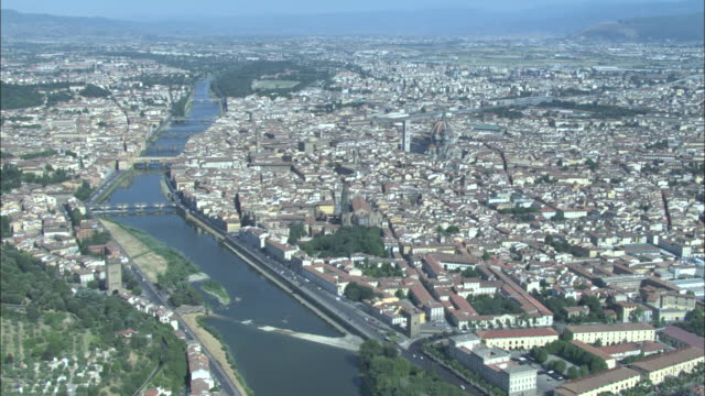 the arno river bisects florence, italy near the basilica di santa maria del fiore. - tuscany stock videos & royalty-free footage