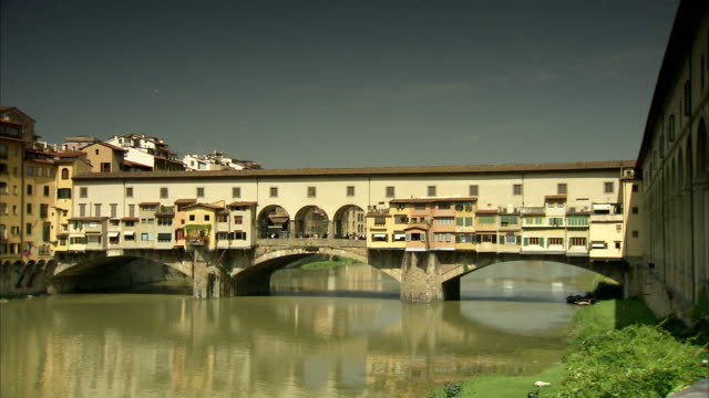 the arno river gently glides under the ponte vecchio. available in hd. - ponte stock-videos und b-roll-filmmaterial