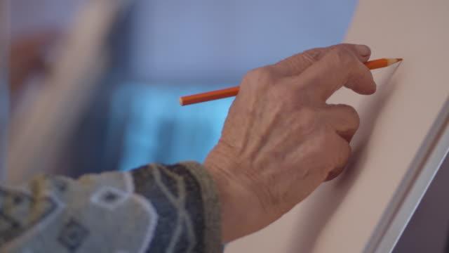 vídeos de stock, filmes e b-roll de a arte da pintura. uma mulher sênior ativa com seus passatempos. pintura artesanal, espaço de trabalho, artesanato, arte, idéias, close-up - ocupação criativa