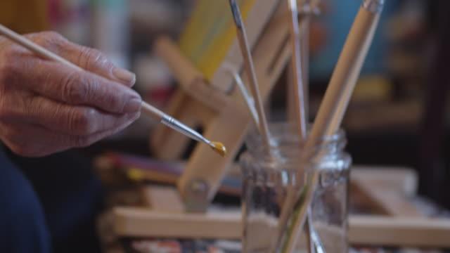 die kunst der malerei. eine aktive seniorin mit ihren hobbys. handgemachte malerei, arbeitsraum, handwerk, kunstwerk, ideen, nahaufnahme - gemälde stock-videos und b-roll-filmmaterial