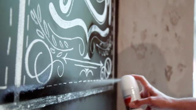 芸術家は彼のチョークの保護のためのドローイングを噴霧します。 - チョークの跡点の映像素材/bロール