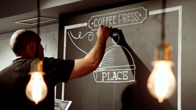 はしごの上に立って、黒い壁にチョークの落書きアーティスト - チョークの跡点の映像素材/bロール