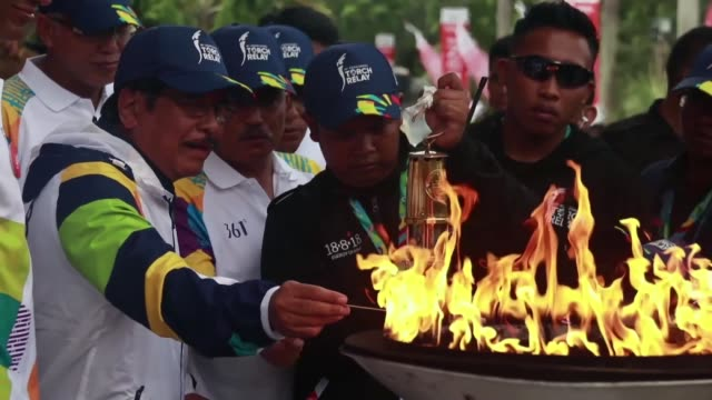 The Asian Games torch arrives by plane at Sultan Iskandar Muda International Airport and is received by Acting Aceh Governor ahead of the opening of...