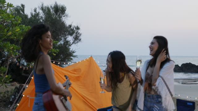 the asian teen girl playing guitar and singing, having fun on the beach with beautiful sea in thailand. - uv protection stock videos and b-roll footage