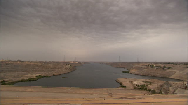 The Aswan High Dam spans across the River Nile near a power plant. Available in HD.
