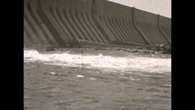 the aswan low dam in egypt 1932 . water flows through the dam, pan of surrounding area downstream . nile riverbanks - dam stock videos & royalty-free footage