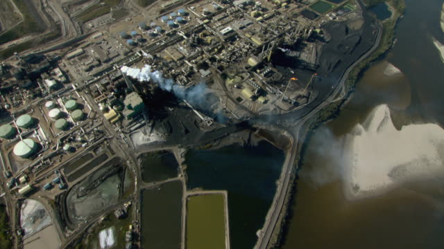 The Athabasca River flows past an oil refinery at Fort McMurray, Alberta, Canada.