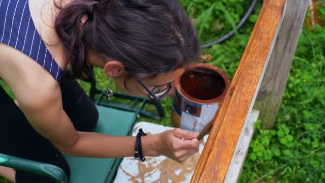 vídeos y material grabado en eventos de stock de la muchacha atractiva adolescente de 15 años pintando la valla en el patio trasero - 14 15 years