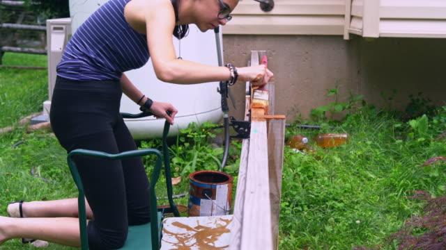 stockvideo's en b-roll-footage met het aantrekkelijke 15-jaar oude tiener meisje schilderij van het hek bij de achtertuin - 14 15 years