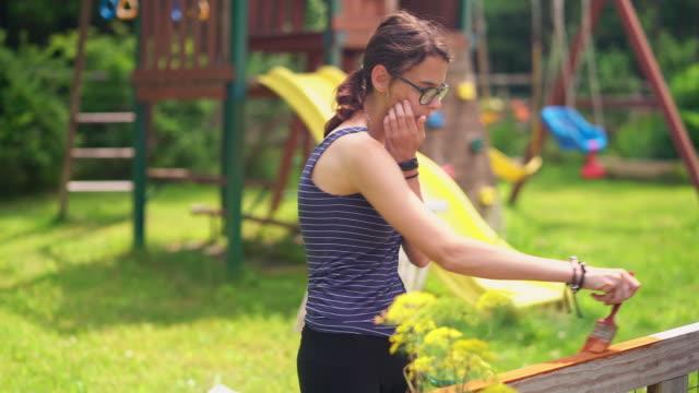 vidéos et rushes de la fille d'attrayant adolescent âgé de 15 ans, peindre la clôture à l'arrière-cour - 14 15 years
